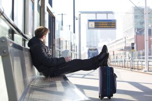 Man sitting at a train station with his feet on a rolling suitcase.