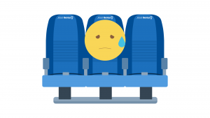 Sad Emoji sitting in the midle seat on the airplane.